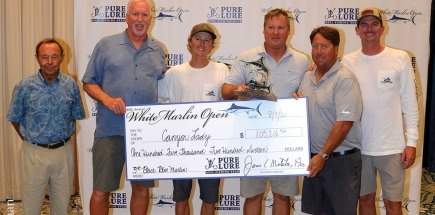 group of men holding check for winning third place in the blue marlin category